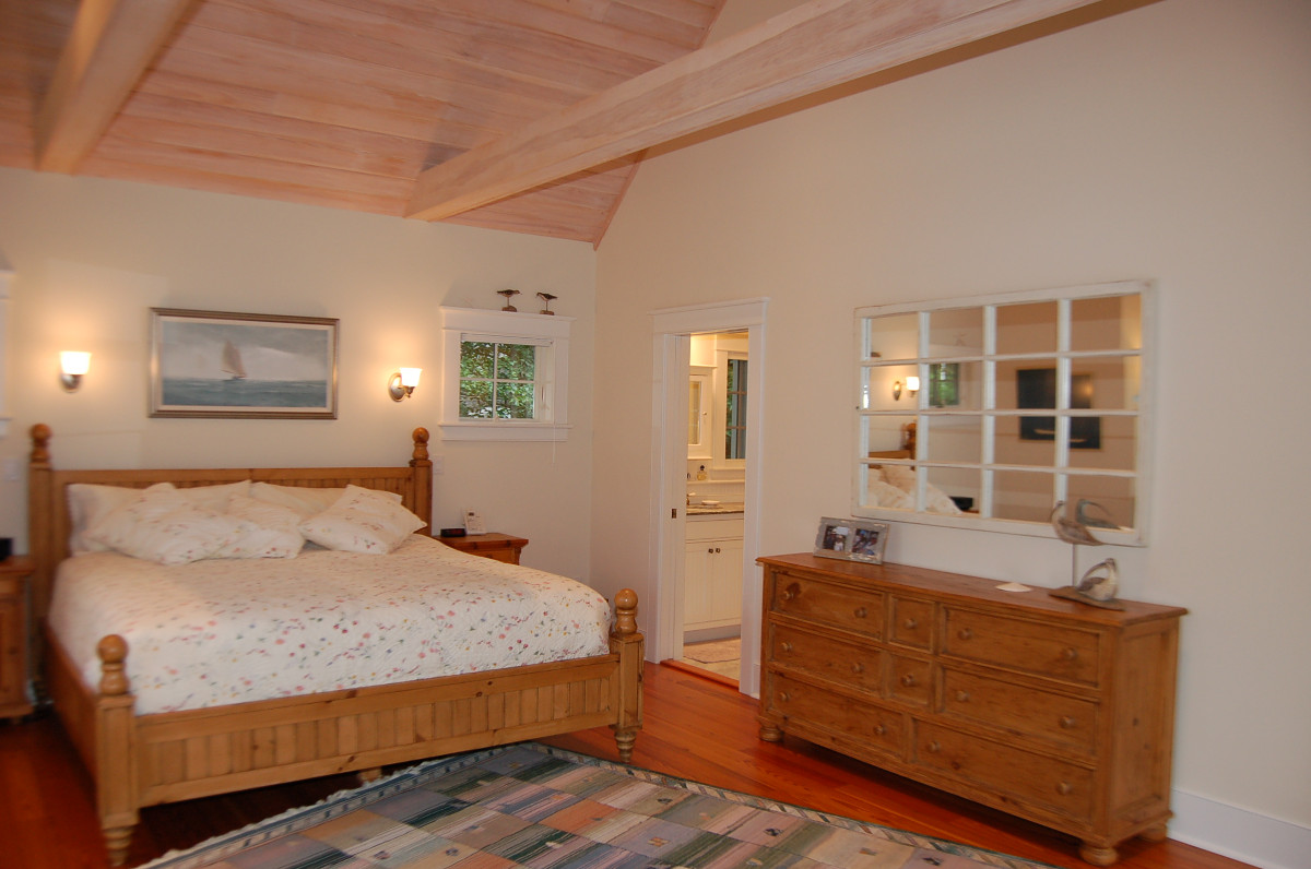 Bedroom with exposed wood celing and beams, hardwood floor