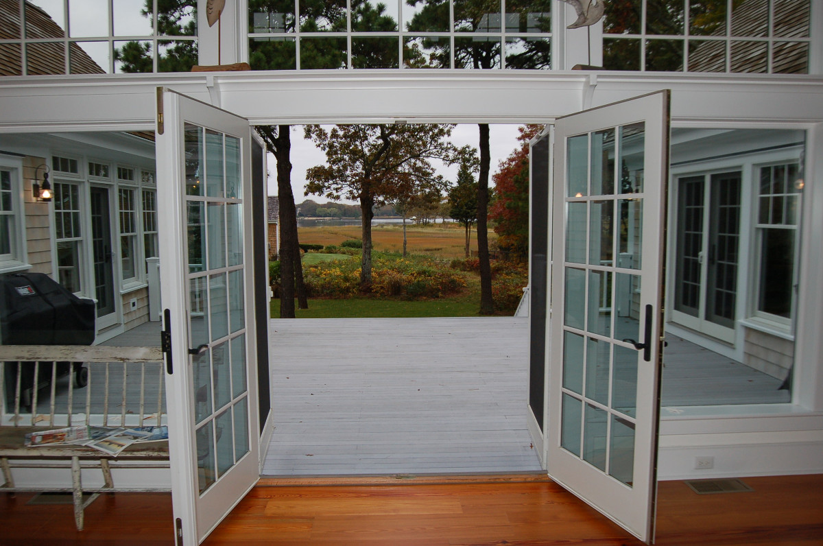 Patio doors and full-size windows opened to outside deck and golf course beyond